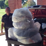 Detective Sean Lewis from the Yorktow Police Department takes 130 pounds of drugs for disposal.